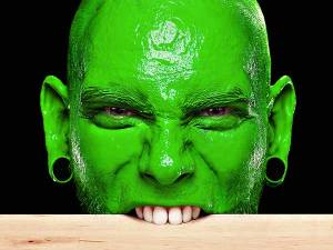 Internet trolls article photo - man with green face bites wood.