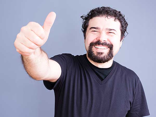 Happy man giving thumbs-up sign.