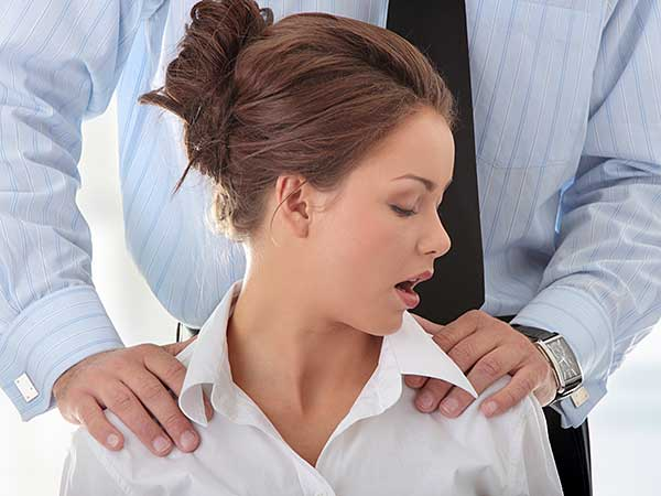 Man massaging woman's shoulders at work.