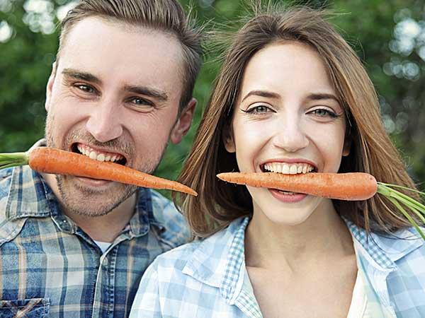 Man and woman biting carrots.