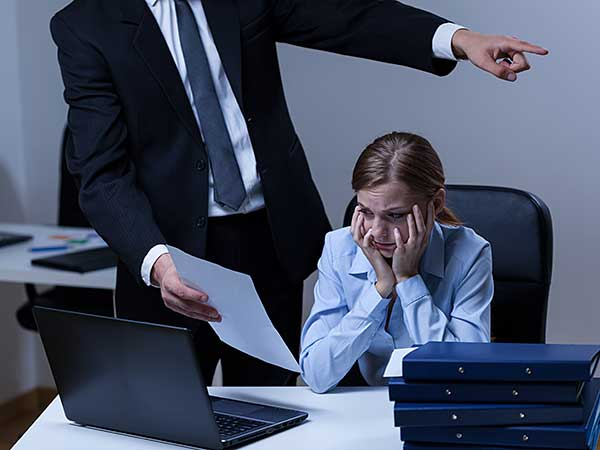 Woman being subjected to harassment at work by bully boss.